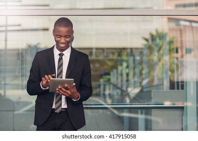 Smiling young African businessman using a tablet in city