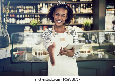 Smiling young African cafe owner extending a handshake while standing in a trendy cafe holding a digital tablet