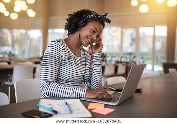 Smiling young African college student sitting on campus working online with a laptop and listening to music on headphones