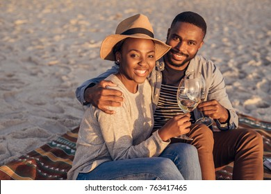 Smiling young African couple sitting on a sandy beach enjoying a glass of wine while watching a sunset
