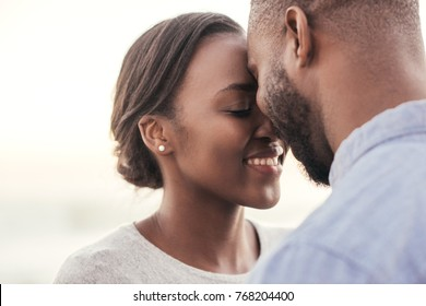 Smiling young African couple standing face to face with their eyes closed while enjoying a romantic sunset at the beach