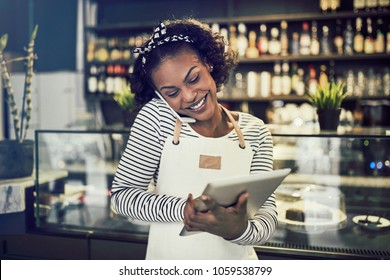 Smiling young African entrepreneur standing in front of the counter of her cafe talking on a cellphone and using a tablet