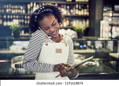 Smiling young African entrepreneur standing in her cafe taking reservations on a cellphone and using a tablet