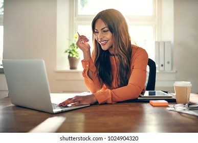 Smiling young African female entrepreneur sitting at a table in her home office working on a laptop