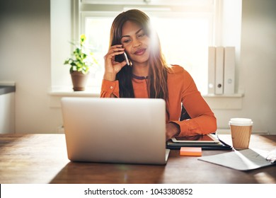 Smiling young African female entrepreneur talking on a cellphone and working on a laptop while sitting at a table in her home office