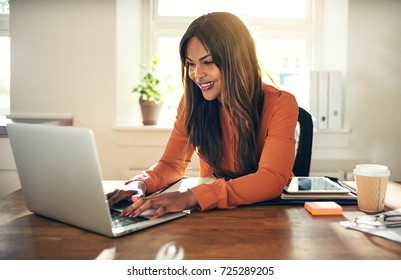 Smiling young African female entrepreneur sitting at a desk in her home office working online with a laptop