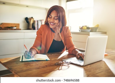 Smiling young African female entrepreneur sitting at a table in her kitchen writing down notes and working on a laptop