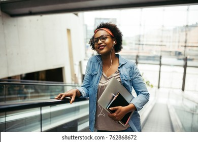 Smiling young African female entrepreneur riding up an escalator in the lobby of a modern office building carrying a laptop and wearing earphones