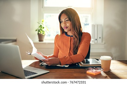 Smiling young African female entrepreneur sitting at a table in her home office reading paperwork and working on a laptop