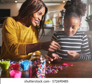 Smiling young African female parent helping cute child in striped shirt make a beaded craft heart shape on table in kitchen