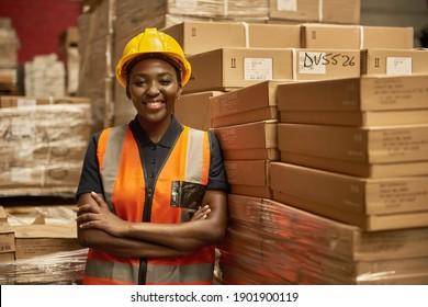 Lächeln Sie junge afrikanische Lagerlerin, die eine Sicherheitsweste trägt und einen Helm trägt, der sich auf einen Stapel von Kisten stützt