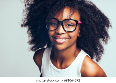 Smiling young African girl with long curly hair wearing glasses while standing alone against a gray background