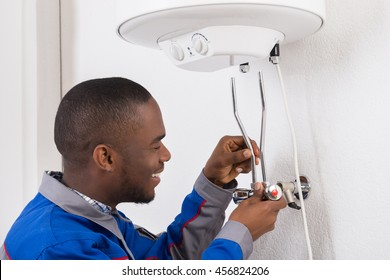Smiling Young African Male Plumber Repairing Electric Boiler