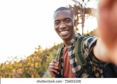 Smiling young African man in a backpack taking selfies while hiking alone up a trail on a sunny day
