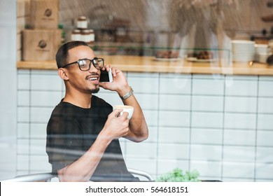 Smiling young african man drinking coffee and talking on mobile phone while sitting in cafe, view through the window