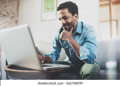 Smiling young African man making video call with friends while sitting on sofa at his modern home.Concept of happy business people.Blurred background, flare effect