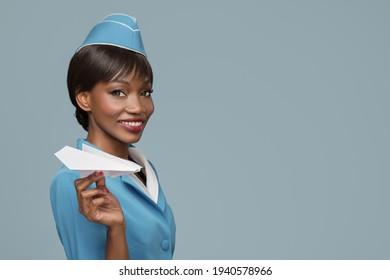 Lächelt junge afrikanische Stewardess, die ein Papierflugzeug in der Hand hält. Blauer Hintergrund.