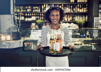 Smiling young African waitress standing in a trendy restaurant holding a tray of colorful drinks