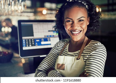 Smiling young African waitress wearing an apron standing by a point of sale terminal while working in a trendy restaurant