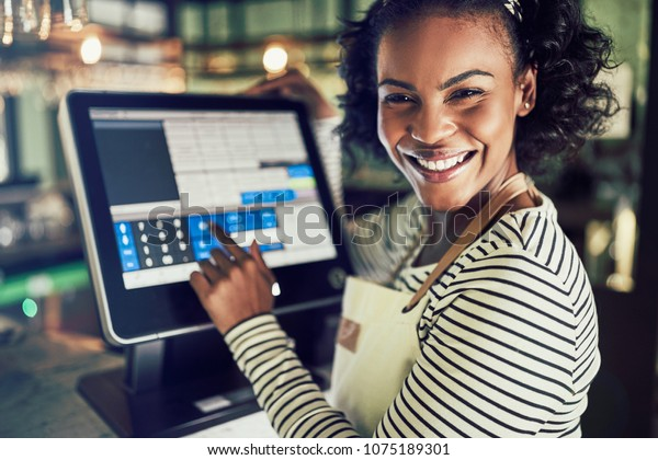 Smiling young African waitress wearing an apron working in a trendy restaurant and using a touchscreen point of sale terminal