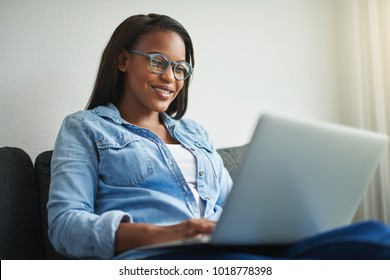 Smiling young African woman browsing the internet with a laptop while sitting on her living room sofa at home