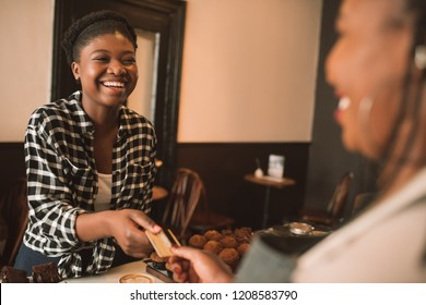 Smiling young African woman giving her bank card to a cafe cashier pay for her cappuccino