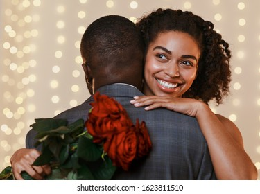 Smiling young african woman holding red roses while hugging her man, having date in restaurant. Happy Saint Valentine's Day