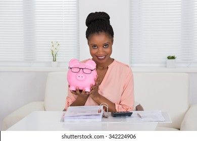 Smiling Young African Woman Holding Piggybank With Eyeglasses