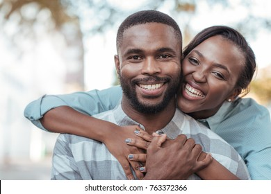 Smiling young African woman hugging her husband from behind while standing together outside on a sunny day
