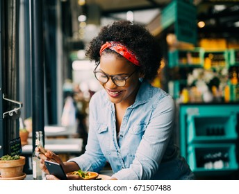 Smiling young African woman reading texts on a cellphone while sitting alone at a counter in a cafe enjoying a meal