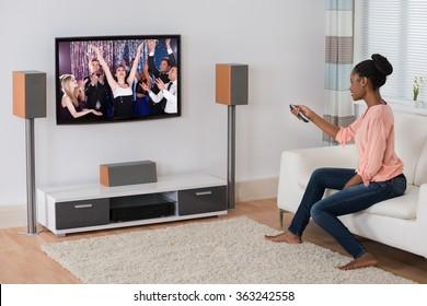 Smiling Young African Woman Sitting On Sofa Watching Movie