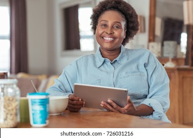 Smiling young African woman sitting at her kitchen table using a digital tablet and eating a healthy breakfast in the morning
