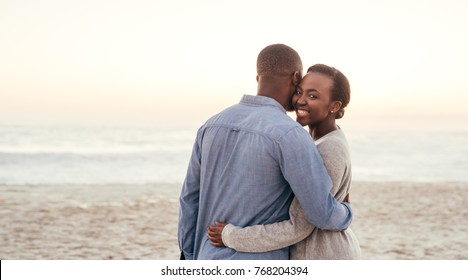 Smiling young African woman standing in her boyfriend's arms while enjoying a romantic sunset together at the beach