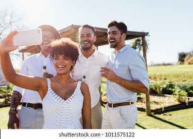 Smiling young african woman taking selfie with friends during outdoors party. Young people having fun at party and taking selfie with smart phone.