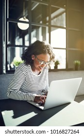 Smiling young African woman wearing glasses sitting alone at a table browsing the internet with a laptop