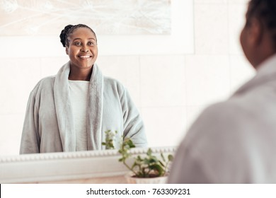 Smiling young African woman wearing a robe looking at her reflection in a mirror while standing in her bathroom in the morning