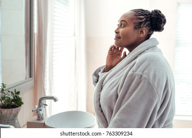 Smiling young African woman wearing a robe standing in her bathroom in the morning looking at her complexion in the mirror