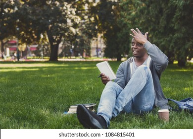 Smiling young african-american man making notes in workbook, got inspiration, sitting on grass in park. Education, inspiration concept, copy space