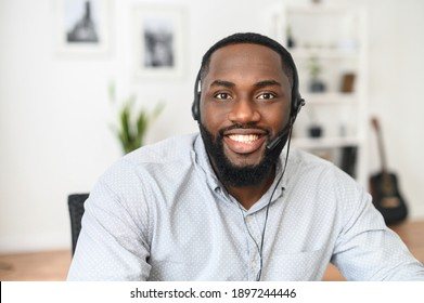 Smiling young African-American office worker wearing a headset and looking at the camera, a positive man with the beard working in the customer service department, making and receiving calls