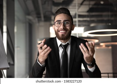 Smiling young Arabian businessman in glasses sit at office desk speak on video call with business partner or client, headshot of happy motivated Arabic male boss engaged in web talk, live broadcast