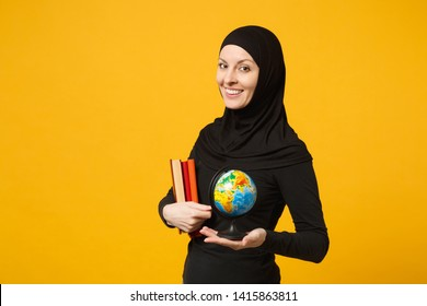 Smiling young arabian muslim student girl in hijab black clothes hold in hands globe, books isolated on yellow wall background, studio portrait. People religious lifestyle concept. Mock up copy space