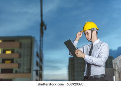 smiling young architect or engineering builder in hard hat with tablet over group of builders at construction site, architect watching some a construction, business, building, industry, people concept