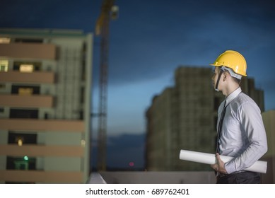 Smiling young architect or engineering builder in hard hat at construction site, architect watching some a construction, business, building, industry, people concept
