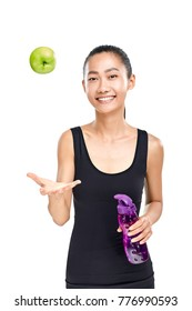 Smiling young Asian athlete holding sipper bottle and throwing up green apple. Sporty woman presenting healthy lifestyle, organic food and healthcare. Half body portrait isolated on white background