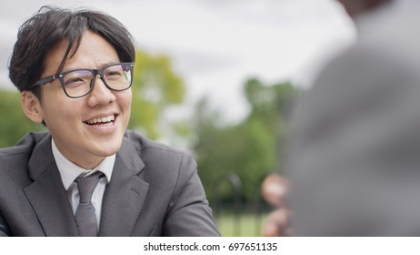 Smiling young asian business man during an outdoor meeting