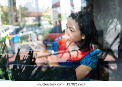 smiling Young Asian Business woman sitting selfie in coffee shop drinking coffee and uses smartphone Laptop shopping online Freelancers working. Online banking marketing shopping educatio
