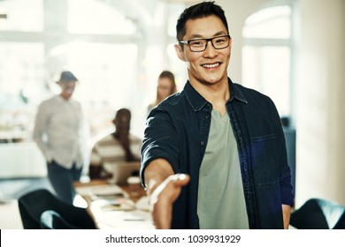 Smiling young Asian businessman extending a handshake while standing in an office with colleagues working in the background