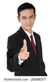 Smiling young Asian businessman with his hand gestures imitating gun pointed straight to camera, isolated on white background