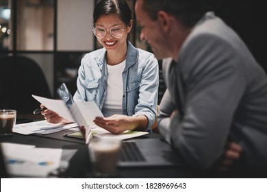 Smiling young Asian businesswoman going over paperwork with a male colleague during a meeting around a boardroom table