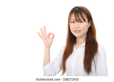 smiling young asian businesswoman with okay gesture